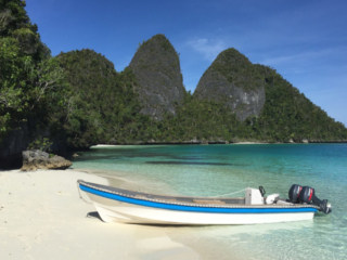 one of Coralia's dive boats at a sandy beach in Raja Ampat Indonesia