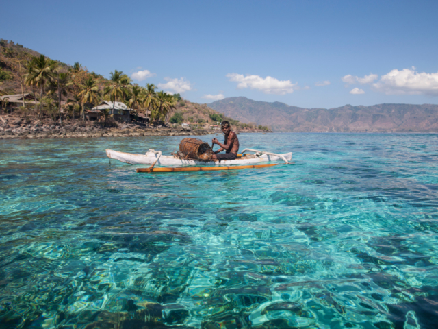 an Alor local in his kayak on the ocean in Indonesia