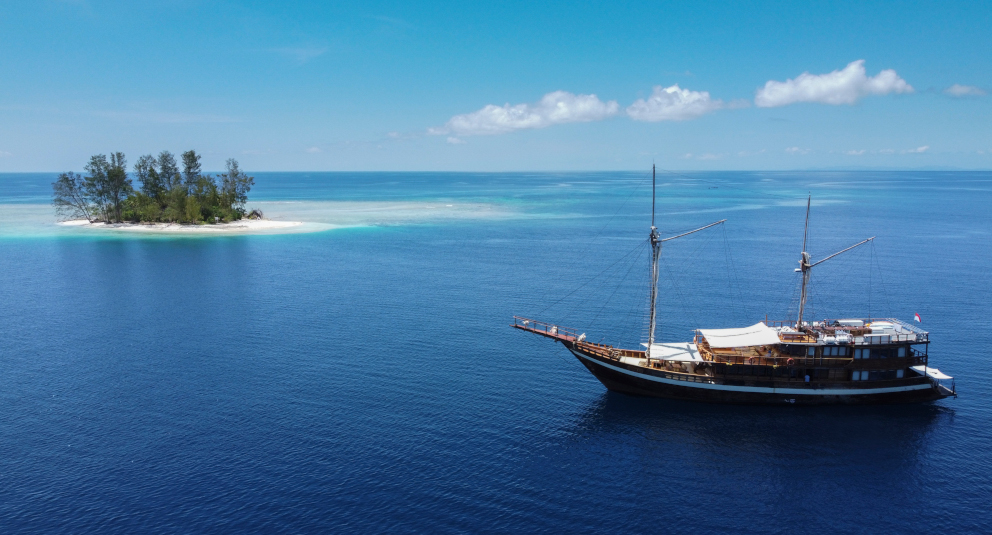 our phinisi cruise ship Coralia at sea next to a tiny tropical island in Raja Ampat